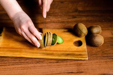 Sliced kiwi on a wooden board.
