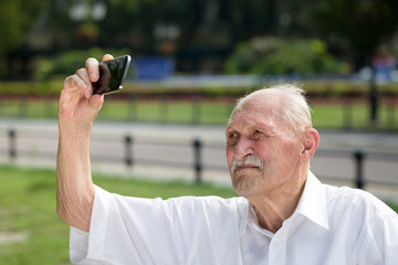 old man taking selfy photo in a park, while sitting on a bench in summer