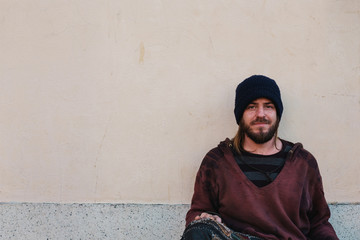 Portrait of young homeless man sitting against blank concrete wall