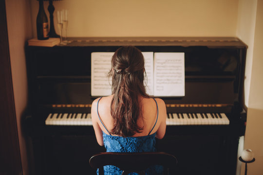 Young woman in blue dress playing the piano using a note sheet