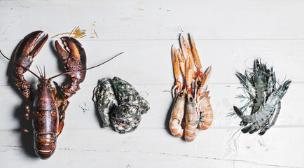 Lobster,oyster,langoustine and shrimp on a wooden surface ready to be prepared for cooking.