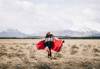 young woman wearing hat and blanket in field next to mountains