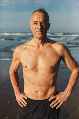 Active senior man - in great shape - standing shirtless on beach in morning sunshine