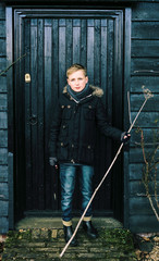 Pre-teen boy in winter clothing standing against a dark door.