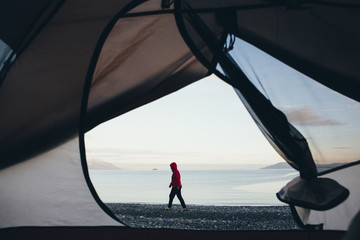 View through doorway of camping tent of woman walking on beach