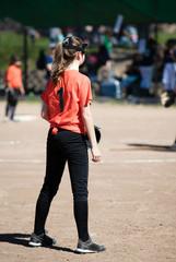 Teenage girl in a softball game wearing protective head gear