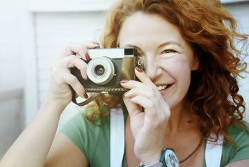Cheerful middle aged lady using vintage camera. Day, outdoor . Happy red hair woman taking picture on retro camera and smiling. Female in green shirt