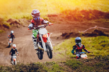Young child racer on a motorcycle participates in motocross cross-country in flight, jumps and takes off on a springboard on the team of rivals. Concept active extreme rest. Wall mural
