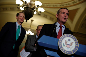 Senator Michael Bennet, accompanied by Senator Ron Wyden, speaks with reporters following the party luncheons on Capitol Hill in Washington