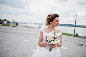 Portrait of a stunning bride posing on the lakeside with a wedding bouquet.