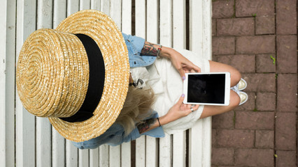 A beautiful young girl in a straw hat is holding a electronic tablet in her hands, sitting on a wooden white bench in the park.