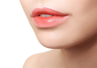 Young woman with beautiful lips on white background, closeup