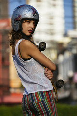 Young girl with skateboard on the Street