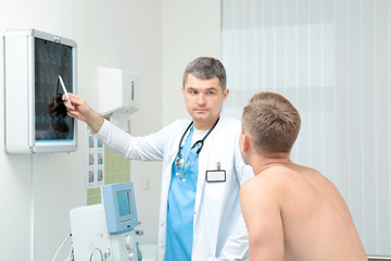 Orthopedist showing x-ray image to patient in clinic