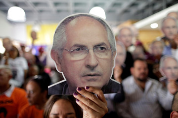 People hold portraits of opposition leader Ledezma during a news conference at the MUD headquarters in Caracas
