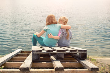 Two little girls sitting on the Bank of the lake embracing on a tree in Sunny summer day.