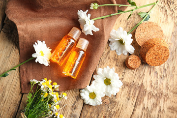 Bottles of essential oil and chamomile flowers on table