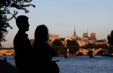 A couple is silhouetted as they enjoy the sunset on the edge of the Seine River near the Pont des Arts and the Ile de la Cite in Paris