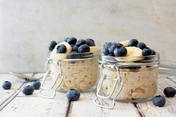 Overnight oats with fresh blueberries and bananas in jars on a rustic white wood background