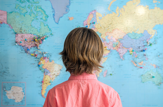 Child stands looking at a map of the world