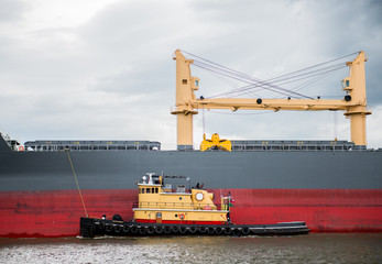Tugboat guides an industrial tanker through a waterway