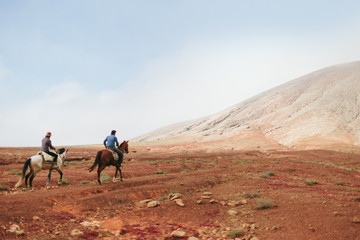 Young Couple Riding Horses in the Desert