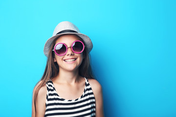 Portrait of beautiful girl with sunglasses and hat on blue background