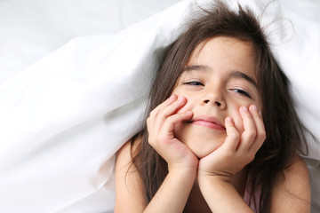 Beautiful little girl sleeping in white bed