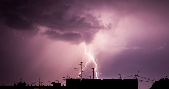 Thunderstorm lightning over city buildings