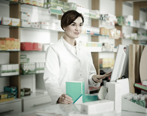 female pharmacist offering assistance at counter in pharmacy