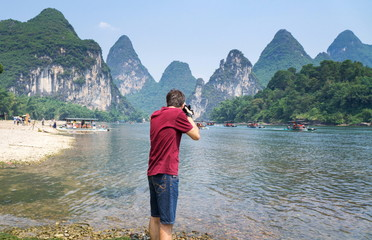 Man photographing scenery of the Li river in Yangshuo China