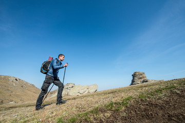 Traveler with trekking sticks and a backpack walks in the mountains
