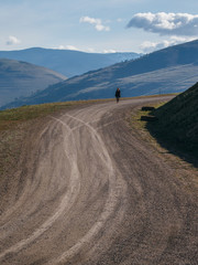 Young woman walking down dirt road with mountains and clouds