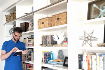 Caucasian man with glasses reading a book next to a bookshelf.