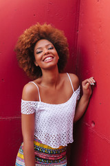 Latin American Afro Woman Against a Red Concrete Background
