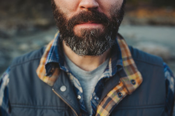 Portrait of young man with thick beard outdoors