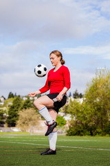 Female soccer player practicing on the field