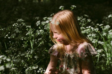 A little girl playing in wild flowers