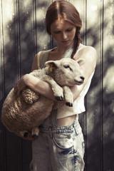 Teenage girl woman holding sheep in sunlight
