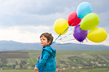 Little boy walking with a bunch of colorful balloons
