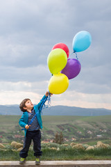 Young boy playing with a bunch of balloons