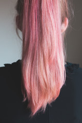 Back view of young woman with bright pink hair worn in a ponytail