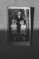old photo in semi shade, family, children with flowers over their faces, hidden