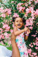 Adorable happy little girl in a tree blossoming with pink flowers