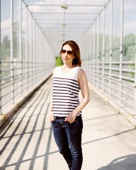 Portrait of a beautiful and fashionable woman standing on a fenced overpass