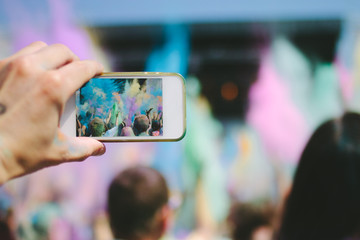 hand with smartphone taking picture of powder throwing crowd at a music festival