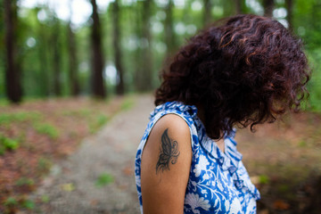 Girl with a tattoo on her forearm in the forest