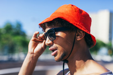 Portrait of a young man wearing a red hat tired after workout.