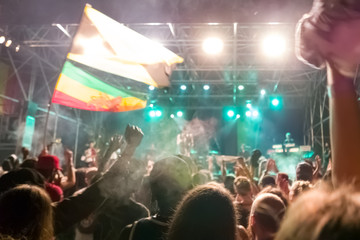 Reggae concert with jamaican flags and cheering crowd