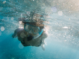 Young woman underwater in a clear sea